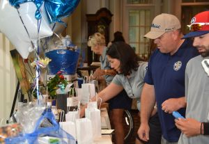 Volunteers prepare the silent auction and raffle